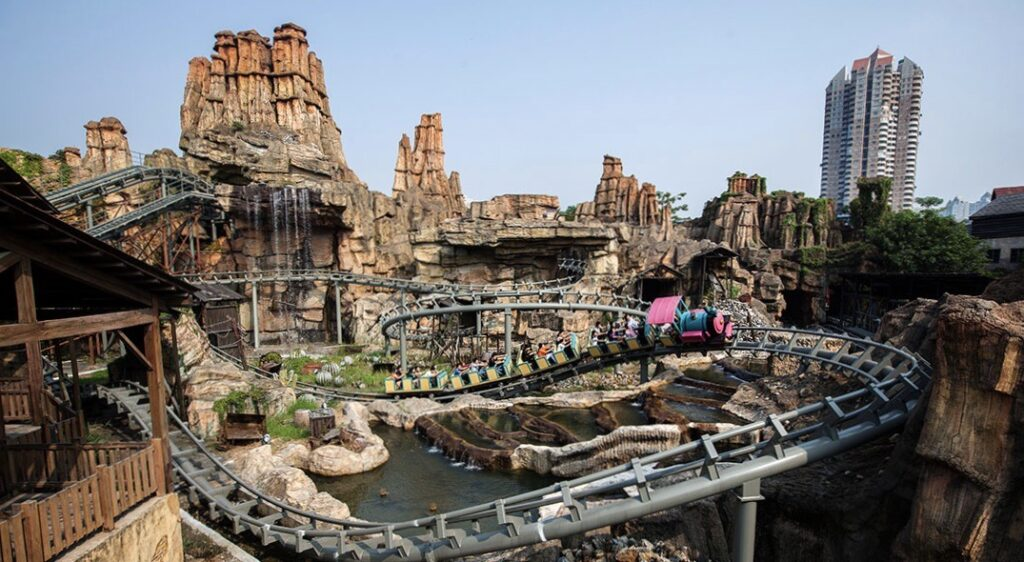A rollercoaster twists through a faux goldmine in Happy Valley theme park. - Shenzhen, China